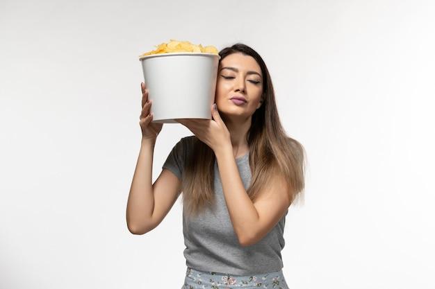 白い表面で映画を見ているチップを保持している若い女性の正面図