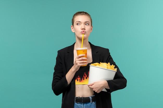 칩 음료를 들고 파란색 표면에 영화를 보는 전면보기 젊은 여성