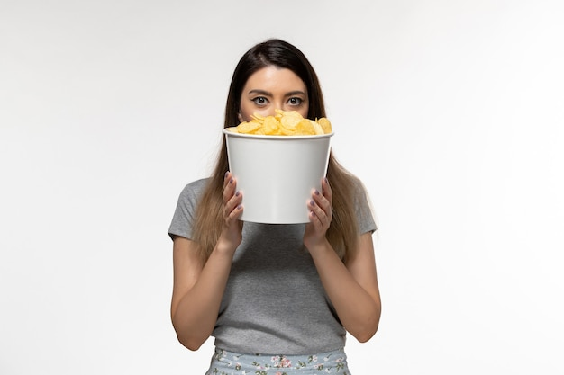 Front view young female holding chips watching movie on white surface