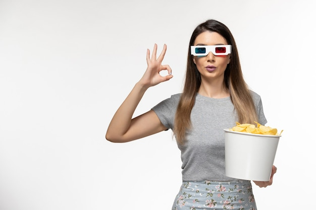 Vista frontale giovani chip di partecipazione femminile mentre si guarda film in occhiali da sole d su superficie bianca