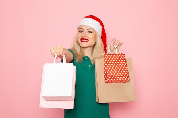 ピンクの壁にパッケージでクリスマスプレゼントを保持している正面図若い女性クリスマス写真モデル年末年始