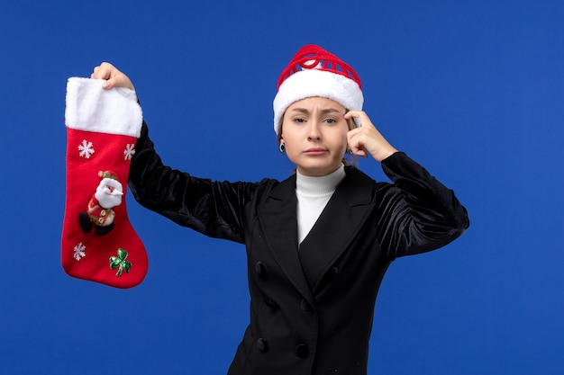 Giovane femmina di vista frontale che tiene il calzino di natale su una vacanza di capodanno della donna dello scrittorio blu