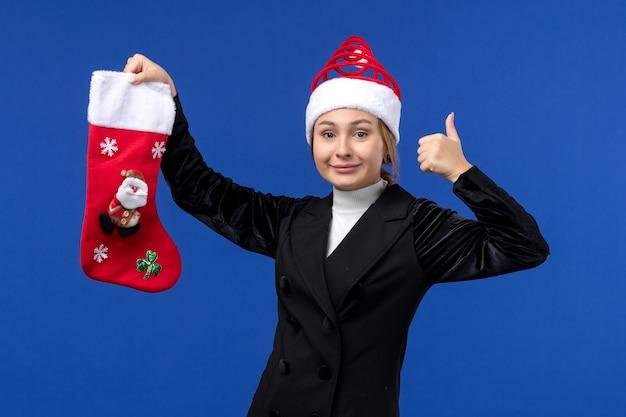 Giovane femmina che tiene il calzino di natale di vista frontale sulla vacanza della donna del nuovo anno del pavimento blu