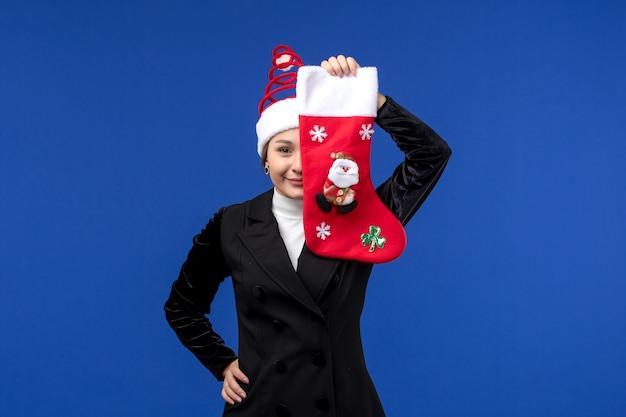 Giovane femmina che tiene il calzino di natale di vista frontale sul nuovo anno blu di festa della donna del pavimento