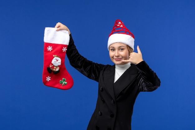 Giovane femmina di vista frontale che tiene il calzino di natale sulla festa della donna del nuovo anno della parete blu