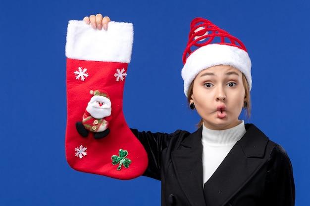 Giovane femmina di vista frontale che tiene il calzino di natale sul nuovo anno di festa della donna della parete blu
