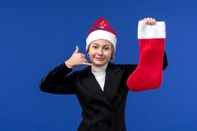 파란색 벽 휴일 새 해 인간에 크리스마스 양말을 들고 전면보기 젊은 여성