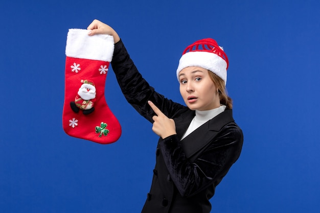 파란색 벽 새 해 여자 휴일에 크리스마스 양말을 들고 전면보기 젊은 여성
