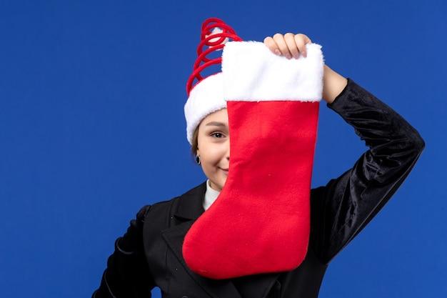파란색 벽 휴일 여자 새 해에 크리스마스 양말을 들고 전면보기 젊은 여성