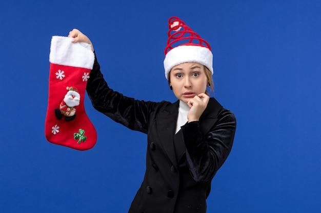 파란색 벽 여자 새 해 휴일에 크리스마스 양말을 들고 전면보기 젊은 여성