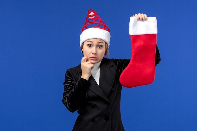 正面図水色の壁の休日の新年の人間のクリスマス靴下を保持している若い女性