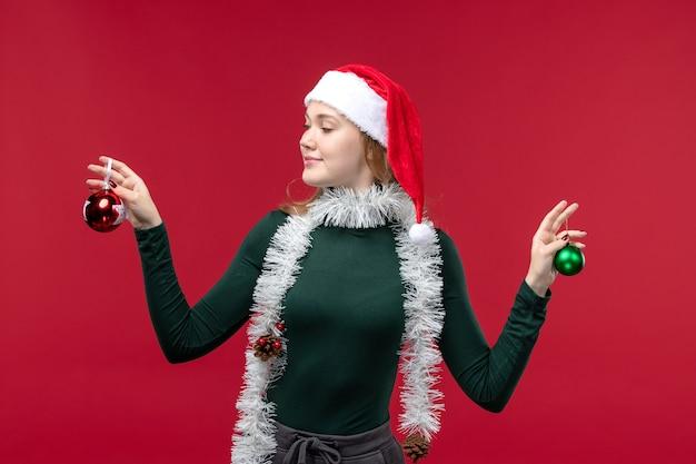 正面図赤い背景にクリスマスツリーのおもちゃを保持している若い女性