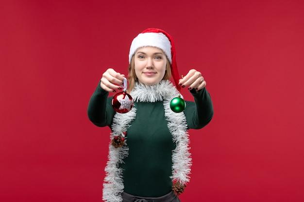 빨간색 배경에 크리스마스 트리 장난감을 들고 전면보기 젊은 여성
