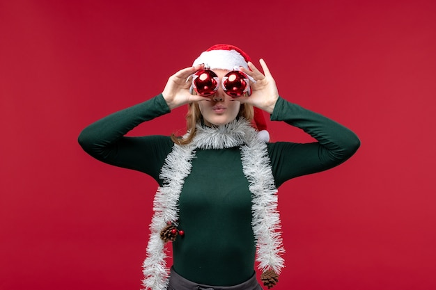 Front view young female holding christmas tree toys on red desk