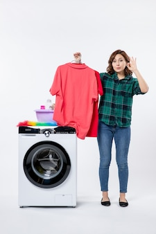 Front view of young female holding clean clothes from washing machine on a white wall