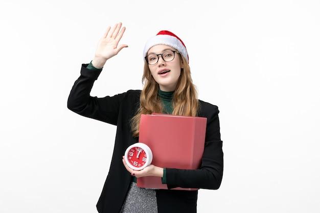 Вид спереди молодая женщина держит часы и файлы на белой стене урок книги колледжа