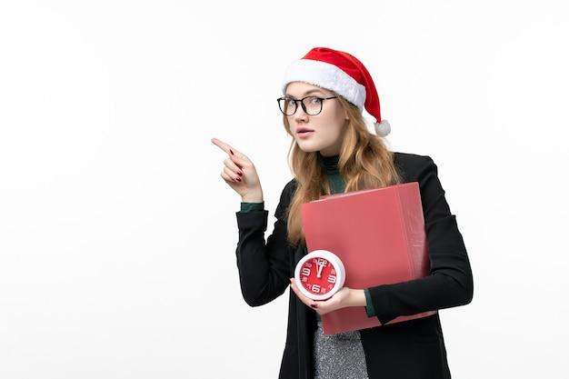 Вид спереди молодая женщина, держащая часы и файлы на белой стене урока колледжа