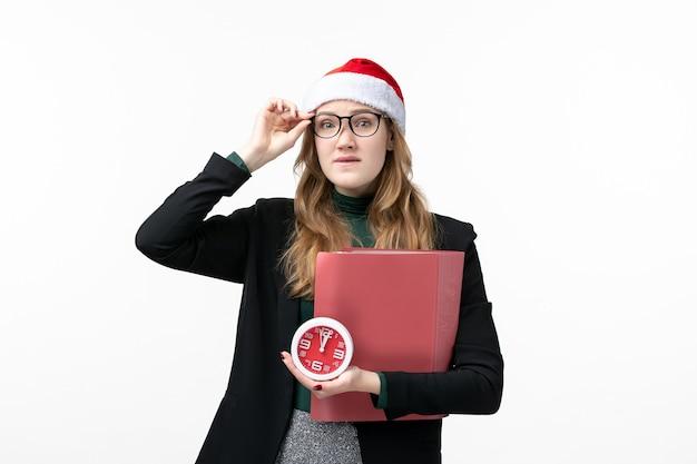 Вид спереди молодая женщина, держащая часы и файлы на белой стене, книга уроков колледжа
