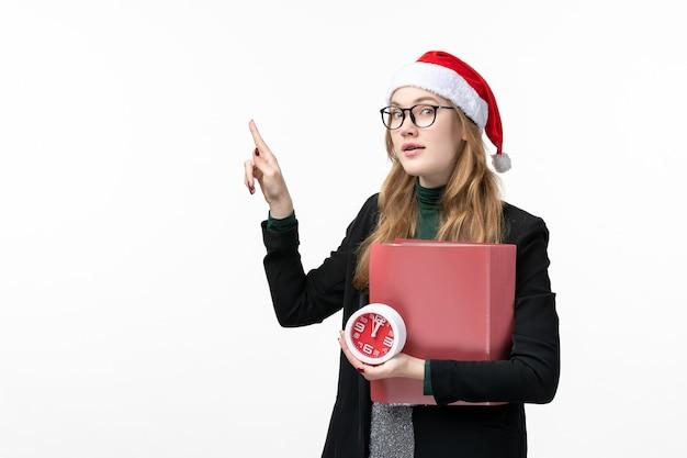 Вид спереди молодая женщина, держащая часы и файлы на белой стене, уроки книги колледжа