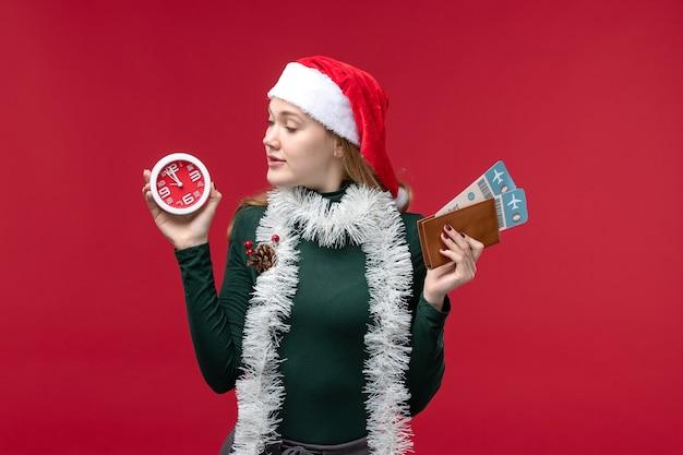 Вид спереди молодая женщина, держащая часы и билеты на красном фоне