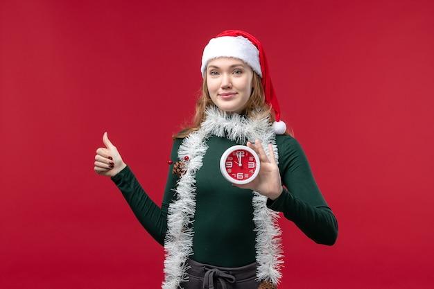 Вид спереди молодая женщина, держащая часы на красном фоне