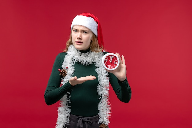 赤い机の上に時計を保持している若い女性の正面図
