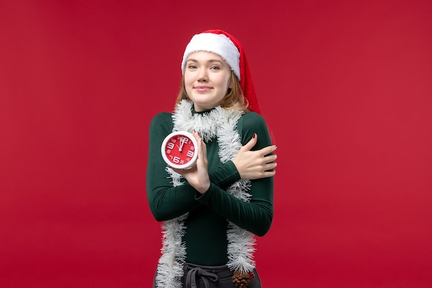 Front view young female holding clock on red floor new year christmas holiday red