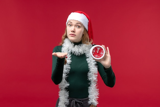 Front view young female holding clock on red floor new year christmas red holiday