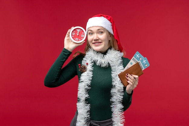 Front view young female holding clock and tickets on a red background