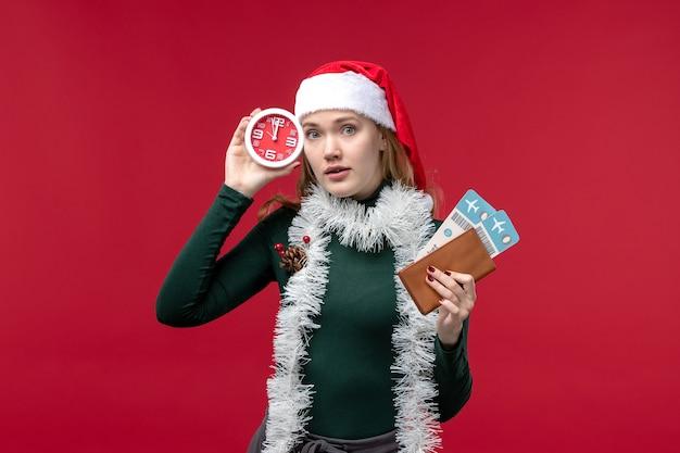 Vista frontale giovane femmina che tiene orologio e biglietti su sfondo rosso