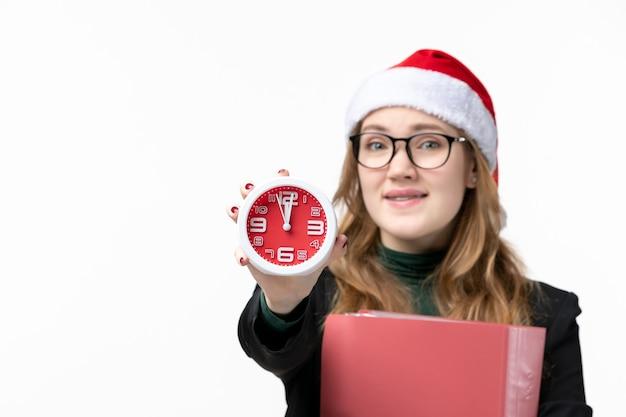 Вид спереди молодая женщина, держащая часы с файлами на белом столе, книга урока колледжа