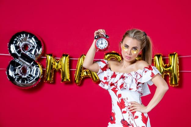 Vista frontale giovane donna che tiene gli orologi a marzo decorati in rosso
