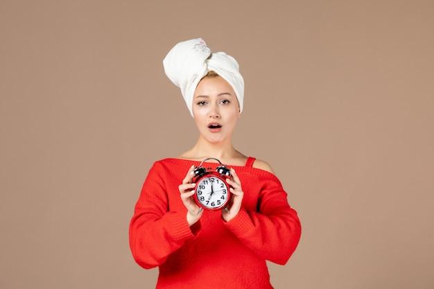 茶色の壁に彼女の頭にタオルで時計を保持している若い女性の正面図