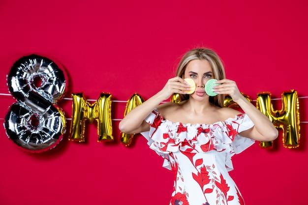 붉은 색으로 장식된 3월에 화장을 지우기 위해 컬러 스폰지를 들고 있는 전면 보기 젊은 여성