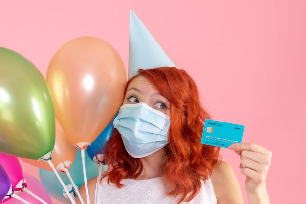 Front view young female holding colorful balloons and bank card on pink