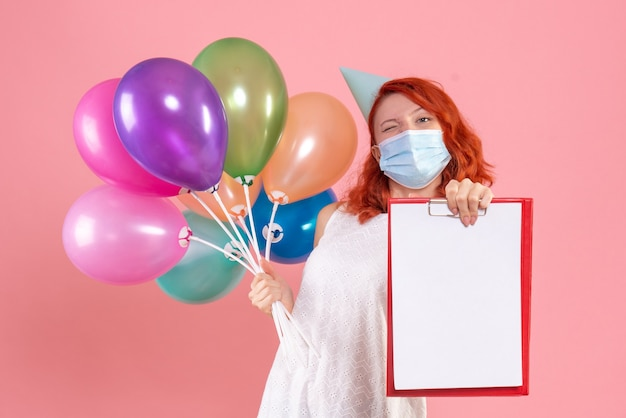 Front view young female holding colorful balloons and file note in mask on pink