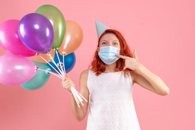 핑크 책상 크리스마스 색상 바이러스 유행성 covid- 파티에 마스크에 다채로운 풍선을 들고 전면보기 젊은 여성