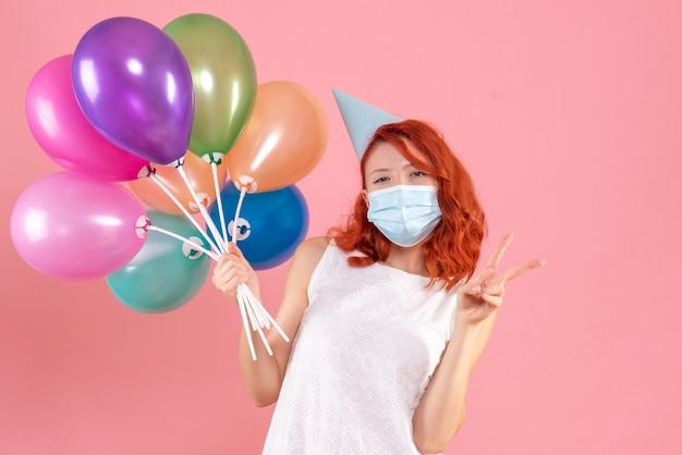 ピンクの床にカラフルな風船を持った若い女性の正面図クリスマスカラーウイルスパンデミック共同パーティー