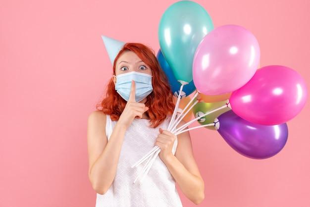 Вид спереди молодая женщина держит разноцветные шары в маске на розовом
