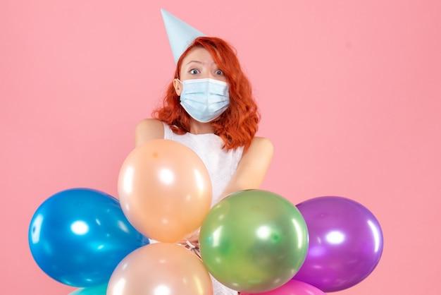 ピンクのマスクでカラフルな風船を保持している正面図若い女性