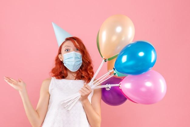 Вид спереди молодая женщина держит разноцветные воздушные шары в стерильной маске на розовом