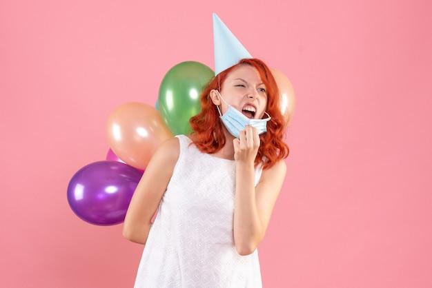 핑크에 살 균 마스크에 다채로운 풍선을 들고 전면보기 젊은 여성