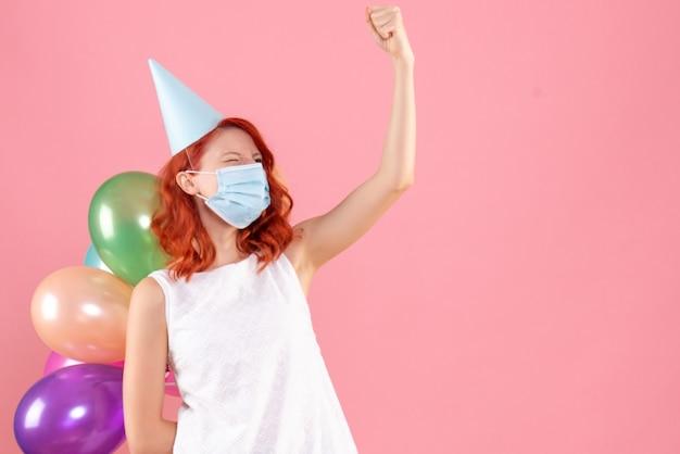 ピンクの滅菌マスクでカラフルな風船を保持している正面図若い女性