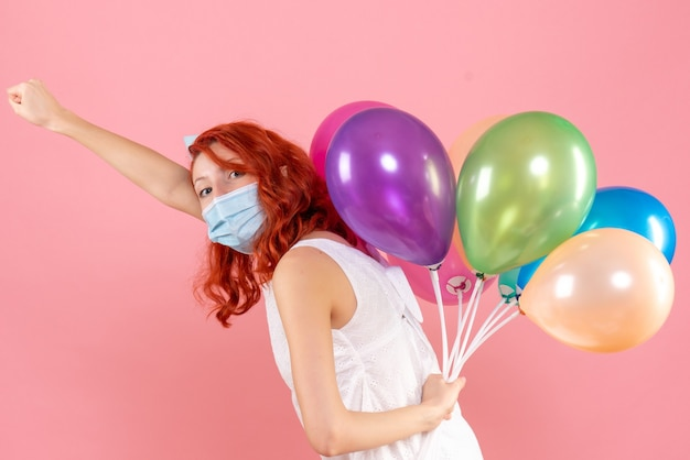 Front view young female holding colorful balloons in mask on pink desk color virus pandemic covid- xmas party