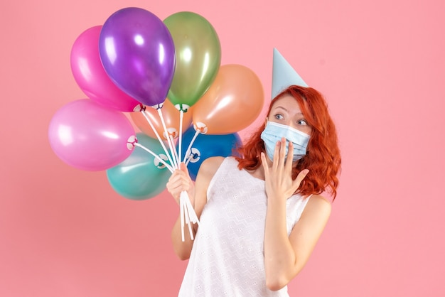 Front view young female holding colorful balloons in mask on pink desk xmas color virus pandemic covid- party