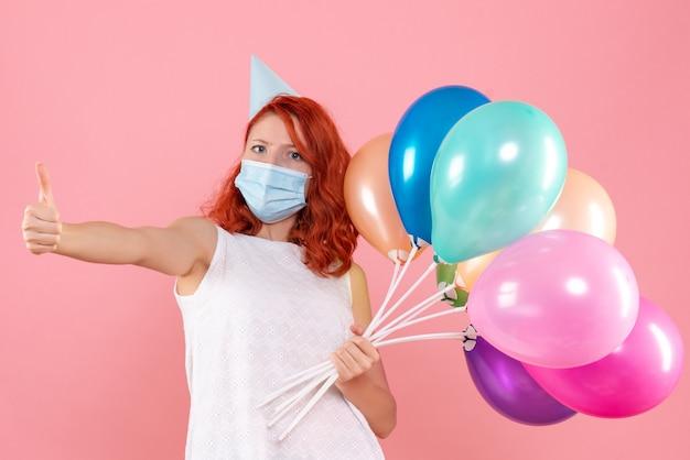 Vista frontale giovane femmina che tiene palloncini colorati in maschera sul rosa