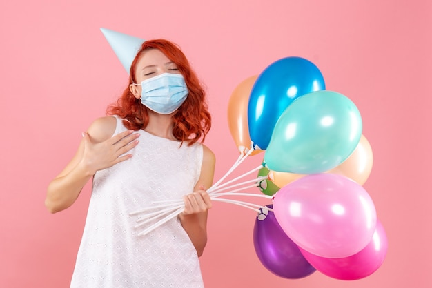 Front view young female holding colorful balloons in mask on a pink