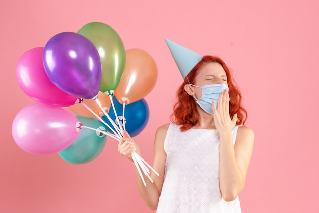 Front view young female holding colorful balloons in mask on pink