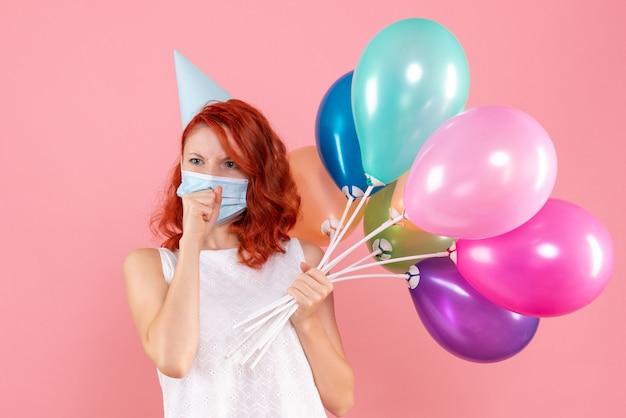 Front view young female holding colorful balloons in mask on the pink