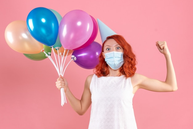 Front view young female holding colorful balloons in sterile mask on a pink